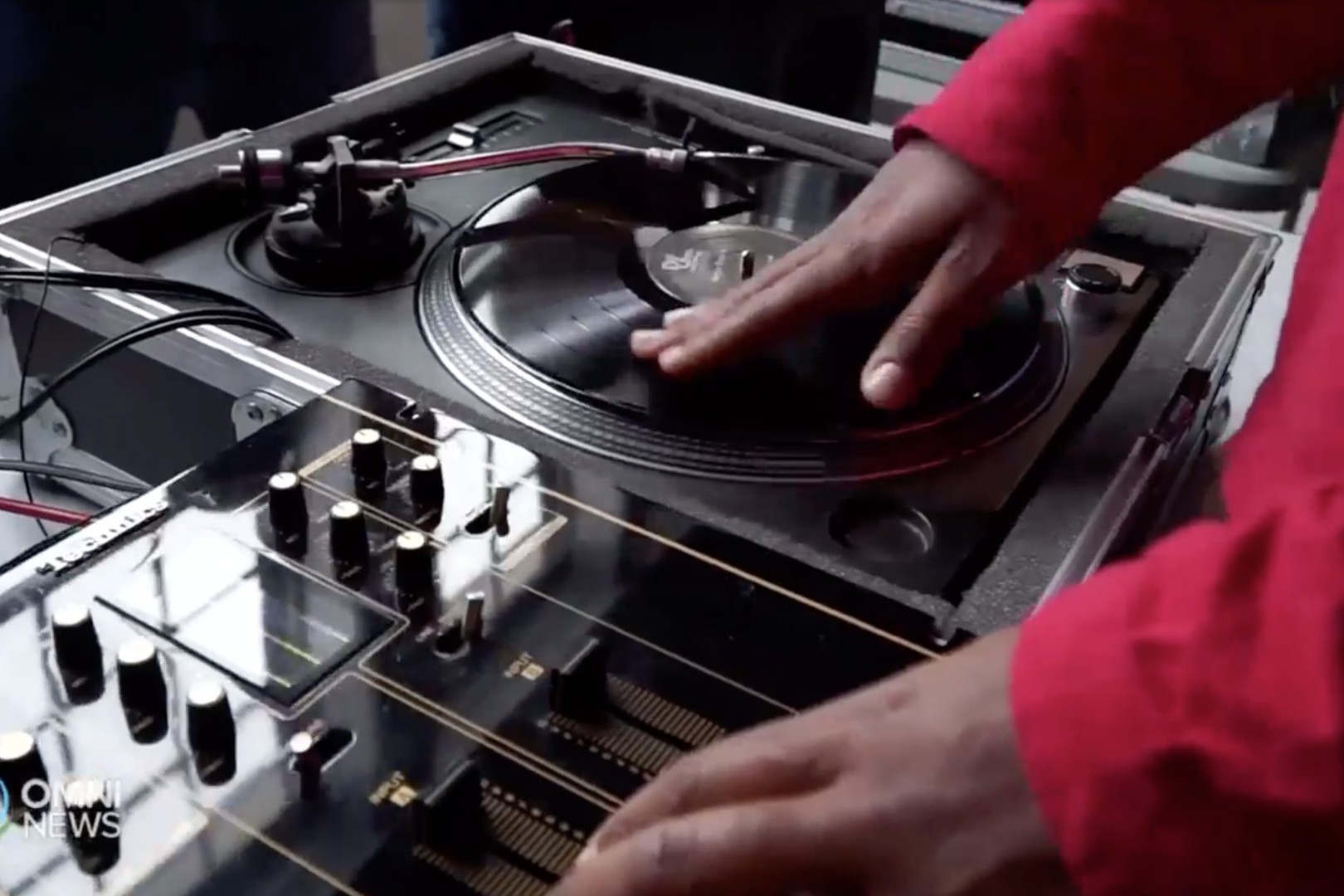 Image of a DJs hands on a turntable and mixer.